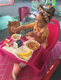 pre-k student eating breakfast in the classroom